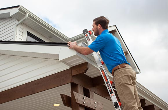 Tyler Battershell, from Apex Inspect, on a ladder inspecting the roof of a home in Fort Wayne, Indiana